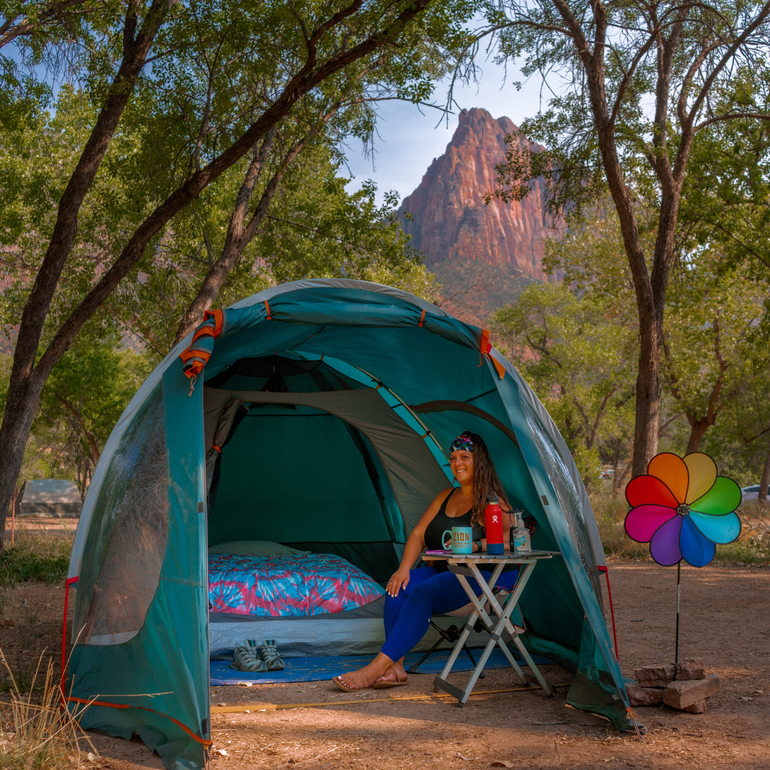 female sitting in tent with her car camping gear while car camping under the mountains of Zion National Park