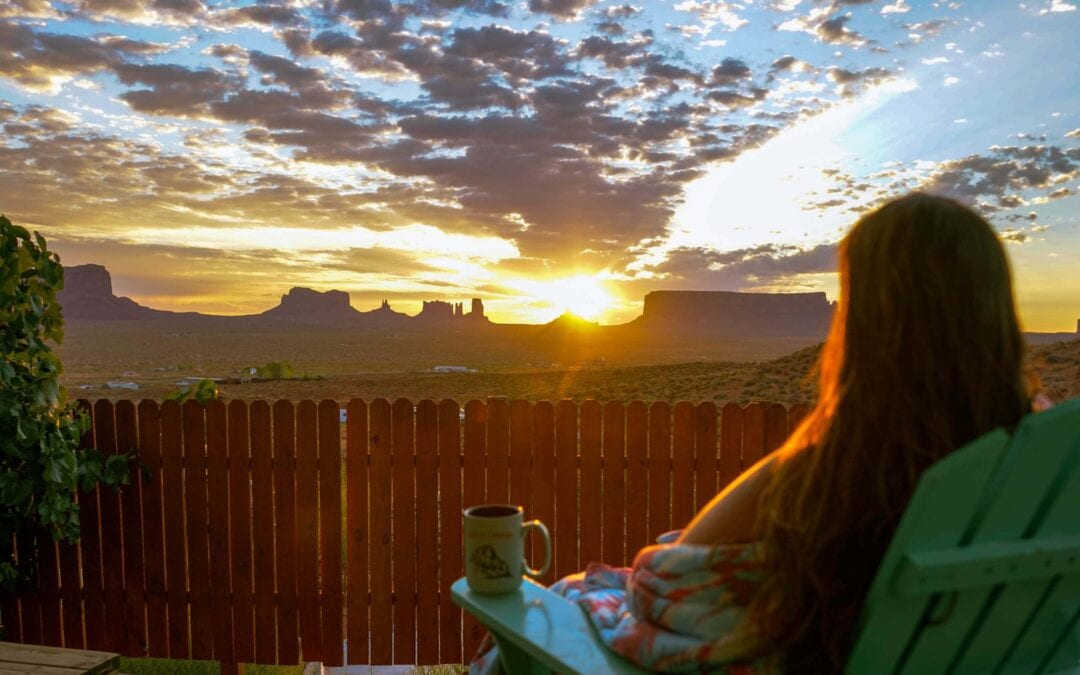 woman sitting on porch watching the sunrise over Monument Valley in the distance